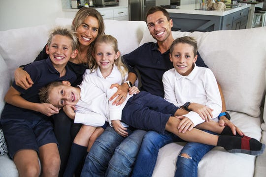 Sophie Chevrier and her husband, Philippe, are elite triathletes and will compete in the Ironman Arizona on November 24th.  They relax at home with their children in Scottsdale, Wednesday, November 20, 2019.  From left clockwise are; Max,13, Sophie, Mia, 8, Philippe, Mathys, 11, and Mael, 6, (lying down).