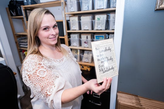 Sara Scherf-Oles holds a print in the workspace of her Marysville home Wednesday, Nov. 13, 2019. Scherf-Oles brings old book pages back to life by adding quotes and artwork to them.