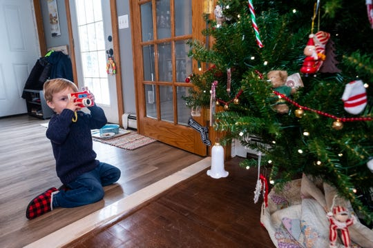 Jack Oles, 3, pretends to take a photo of the Christmas tree in his family's Marysville home Wednesday, Nov. 13, 2019.