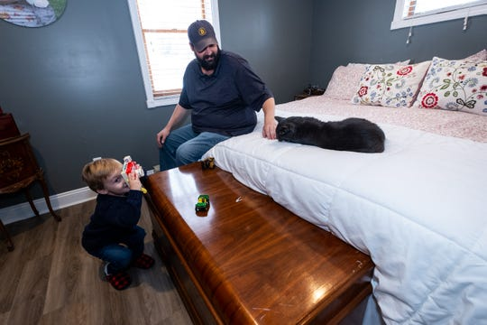 Jed Oles plays with his cat Smokey while his son Jack, 3, pretends to take a photo with his toy camera Thursday, Nov. 13, 2019, in the master bedroom of their Marysville home.