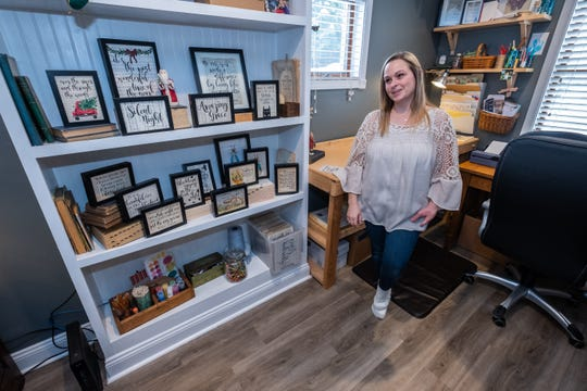 Sara Scherf-Oles talks in the workspace of her home Wednesday, Nov. 13, 2019, in her Marysville home. Scherf-Oles brings old book pages back to life by adding quotes and artwork to them.