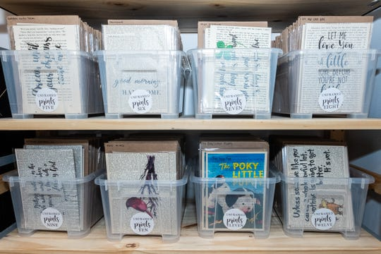 Plastic bins full of prints are arranged on shelves in Sara Scherf-Oles' workspace.