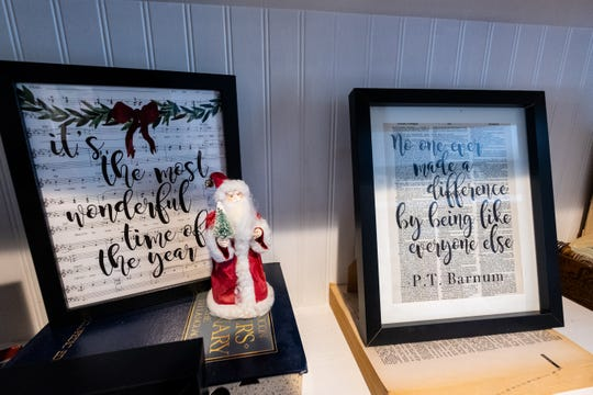 Artwork created by Sara Scherf-Oles is displayed on shelves in her house. Scherf-Oles brings old book pages back to life by adding quotes and artwork to them.