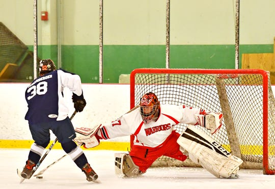 Dallastown's Trae Schanberger, left, works to score a goal while Susquehannock's goalie Brady Frey defends during ice hockey action at York Ice Arena in York City, Wednesday, Nov. 20, 2019. Dawn J. Sagert photo