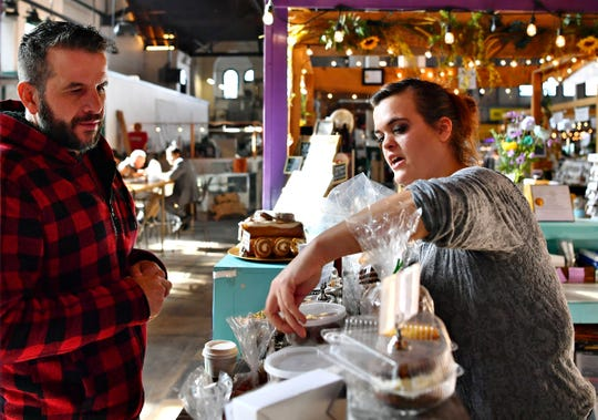 Owner Laura Small, right, offers suggestions for Barry Swope, of York City, as he selects treats for his sister to try at Safe & Sweet, a gluten-free, sugar-free, keto-friendly bakery, at Central Market House in York City, Thursday, Nov. 21, 2019. Dawn J. Sagert photo