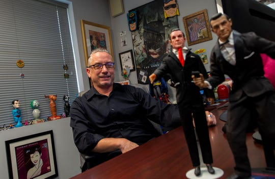 Todd Sheffer, production manager at Hake's Auctions, sits at his desk with two James Bond action figures that date back to the 1960s (left) and 2000s (right).