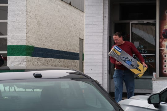 A law enforcement official carries a confiscated chainsaw out of Royal Crown Pawn in Greece Thursday.