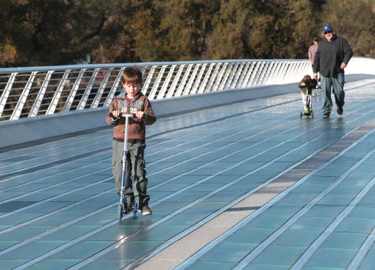 Cillian Braswell, 7, of Red Bluff scoots ahead of his 4-year-old brother, Sawyer, and dad Joseph on a dry, breezy day in the mid-60s on the Sundial Bridge in Redding on Wednesday, Nov. 20, 2019.