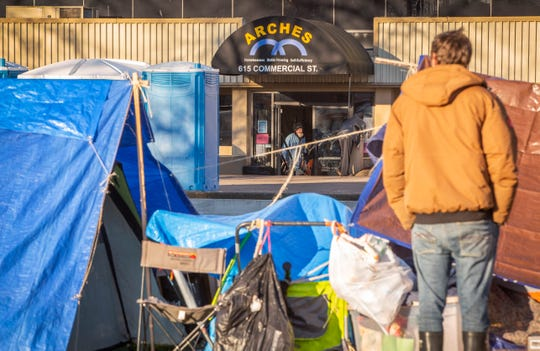 Tents line the sidewalk in front of the ARCHES building on Commercial Street in Salem November 21, 2019. The tents have spread to the sidewalk across the street from ARCHES as well. In addition to the tents there are shopping carts, bicycles and other items lining the streets.