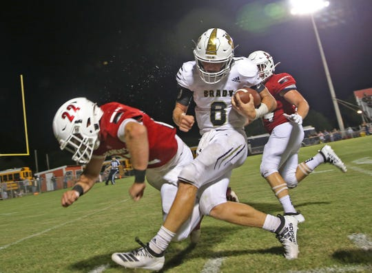 Walker Bauer, center, makes contact with a Ballinger defender, left, during a game Friday, August 30, 2019.