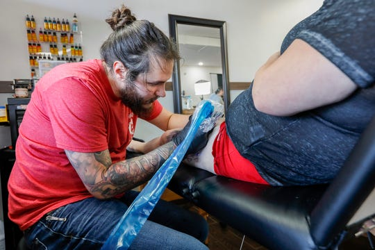 Justin Fleetwood works on a tattoo at The Bearded Lady Tattoo Parlor on Wednesday, Oct. 23, 2019.