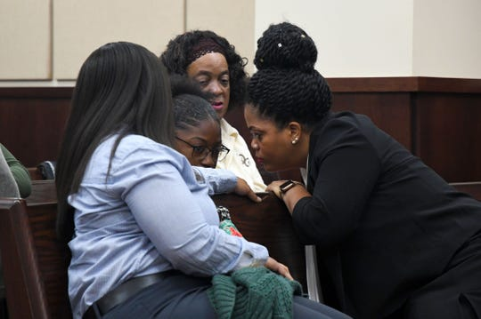 Henry Segura's family members whisper with one another about the sentencing phase for Segura.