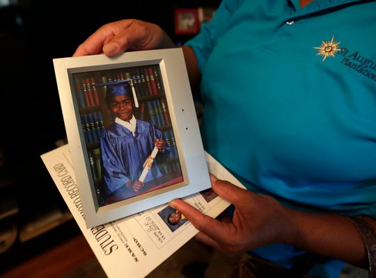 Tawana Mitchell, grandmother of 16-year-old Amarion James who was shot and killed last weekend, holds a kindergarten graduation photo of James.