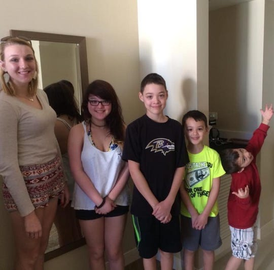 Alicia Devine poses for a photo with her half siblings Ashley, Anthony, Alex, and Danny Wong the first time they met in 2014.