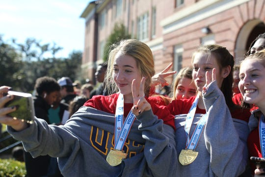 Leon sophomore Naomi Somerset and senior Caroline Curry take a photo after Leon's volleyball team captured a Class 6A state championship and celebrated on its grounds on Nov. 21, 2019.