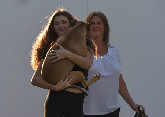 Brandi Bragdon cuddles Kiki while with her mother Christine Bragdon in the driveway of their home in Palm City. Brandi had to convince her parents to allow her to keep the dog by first telling them she just wanted to foster Kiki.
