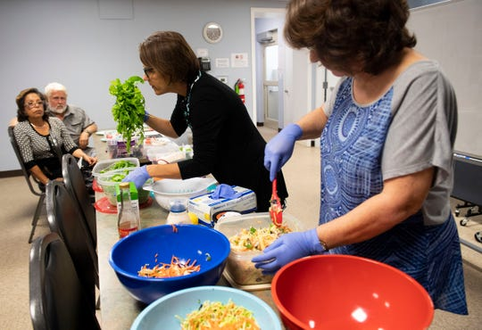 "Marybeth Peña, Martin County Health Department nurse program specialist, smells a handful of fresh arugula Monday, Nov. 4, 2019, during a diabetes prevention workshop at the Golden Gate Center for Enrichment in Stuart. The workshop, a partnership between the health department and House of Hope, offers recipes and constructive cooking advice to people living with diabetes. The produce used, like the arugula, comes from the House of Hope production farm and other items, like chickpeas or pasta, comes from the House of Hope pantry. ""This is a fantastic class because I had high blood pressure, high cholesterol, and because of this I beat it,"" said co-chef Nellie Sanz (right), of Palm City. ""My doctor is very happy."""