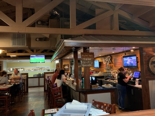 The Tin Roof Bar & Grill features wooden seats and benches with tabletops festooned with local business ads.