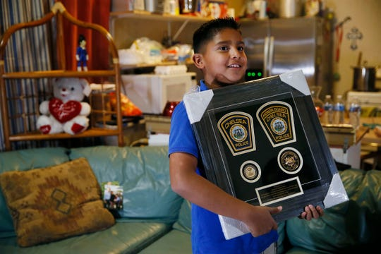 Walmart hero Eduardo Mier shows off police badges gifted to him by University of Massachusetts Boston police and other departments around the country. He is pictured at his home on Wednesday, Nov. 20, in El Paso. Mier pulled his mother out of the store to safety after they both witnessed people killed and she was paralyzed in shock.