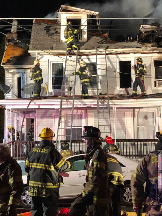 Firefighters swarm 815-813 Archer St. in Millville Wednesday night.