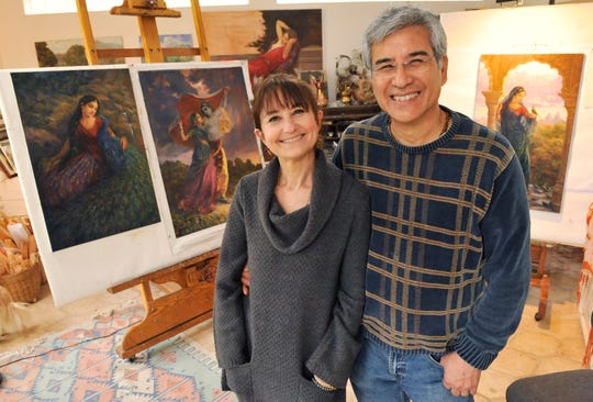 "Miriam Briks and Kevin Albert Yee are married and work together painting scenes from Indian scriptures. Behind them are ""Radha and the Peacock,"" left, ""The Storm"" and ""Lalita."""