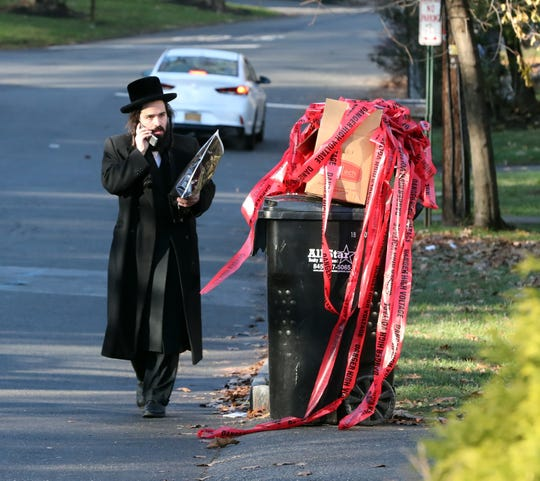 A man walks by the crime scene tape from a stabbing that occurred the day before on Howard Drive In Monsey Nov. 21, 2019.