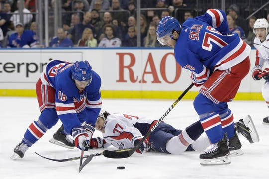 Washington Capitals' T.J. Oshie (77) fights for control of the puck with New York Rangers' Brady Skjei (76) and Ryan Strome (16) during the first period of an NHL hockey game Wednesday, Nov. 20, 2019, in New York.
