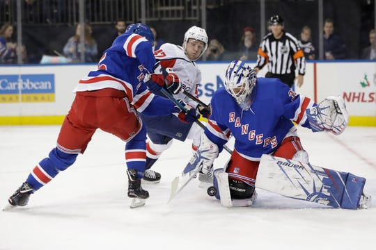 New York Rangers goaltender Henrik Lundqvist, right, stops a shot on goal by Washington Capitals' Beck Malenstyn, center, as Libor Hajek defends during the first period of an NHL hockey game Wednesday, Nov. 20, 2019, in New York.