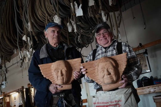 (left to right)Tony Bosworth and Gary Deshong, who both volunteer on the Kalmar Nyckel ship have logged more than 10,000 hours of service. The two hold wood carvings of their faces that will be placed on the stern of the ship to honor their service.