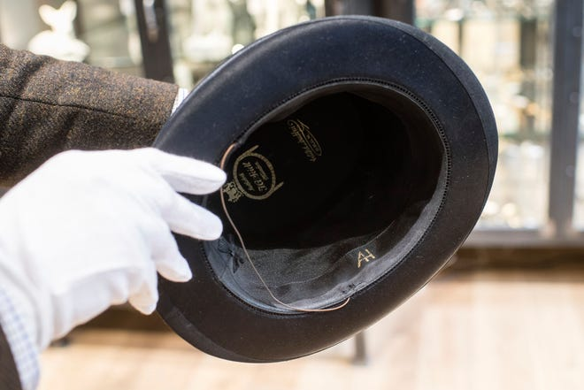 A man holds a hat with the initials of Adolf Hitler prior to an auction in Grasbrunn, Germany, Wednesday, Nov. 201, 2019. A Jewish group has sharply condemned an auction of Nazi memorabilia in Germany.