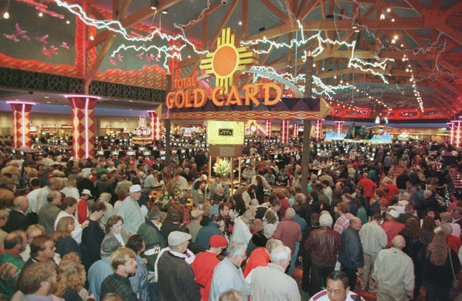 In this photo from Nov. 13, 1997, gamblers pour into the Harrah's Cherokee Casino in Cherokee, N.C. In 2021, an official with the Eastern Band of Cherokee Indians said the casino generates $500 million annually for the tribe, but as legalized gambling expands throughout the country and threatens gambling revenues, the Cherokee tribe hopes to draw new income from medical marijuana sales.