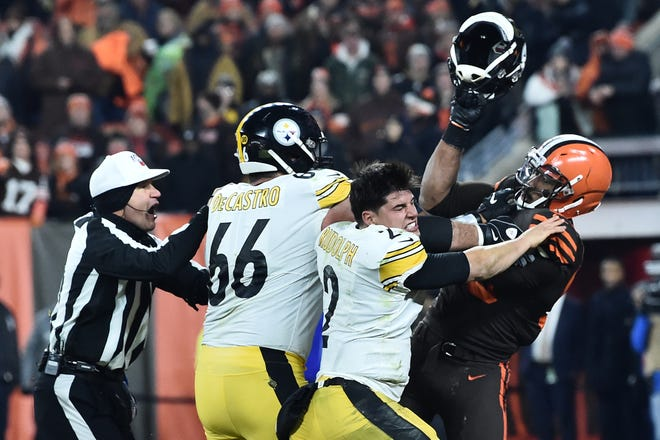 Cleveland Browns defensive end Myles Garrett (95) hits Pittsburgh Steelers quarterback Mason Rudolph (2) with his own helmet as offensive guard David DeCastro (66) tries to stop Garrett during the fourth quarter at FirstEnergy Stadium.