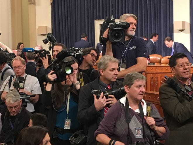 USA TODAY photographer Jack Gruber, in the middle holding his camera, waits for witnesses to enter the hearing room to testify in the impeachment inquiry of President Trump.