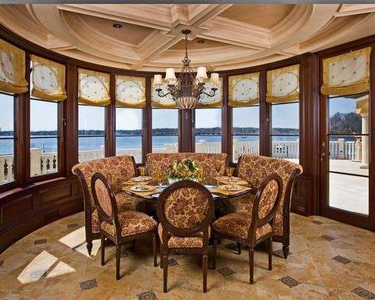 The kitchen offers coffered ceilings marble tile and custom windows to deck.