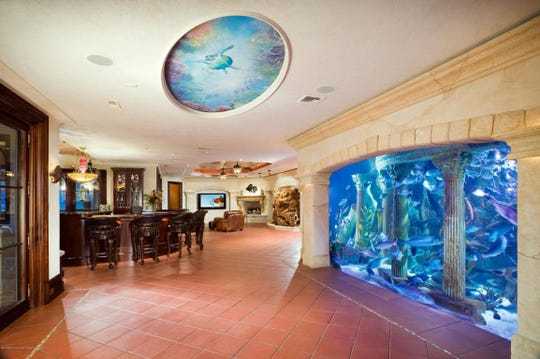 The lower level features marble flooring and a 20,000-gallon aquarium with assorted fish.