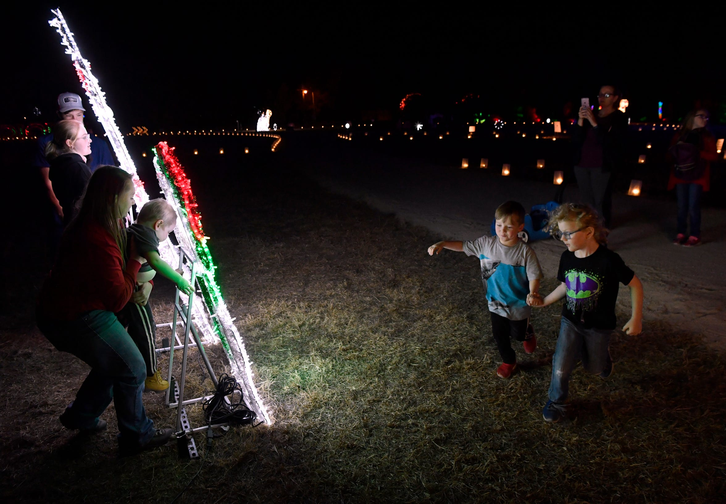 Matthew Keeton, 5, leads his cousin Chandler Batchelor, 4, to the rear of lighted cutouts Nov. 19  at Winter Lightfest.