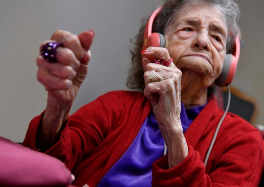 "Shaking her fists, clapping her hands, and letting out the occasional ""Whoop!"", Pansy Hale, 101, enjoys the Elvis Presley music playing through her headphones Oct. 31."