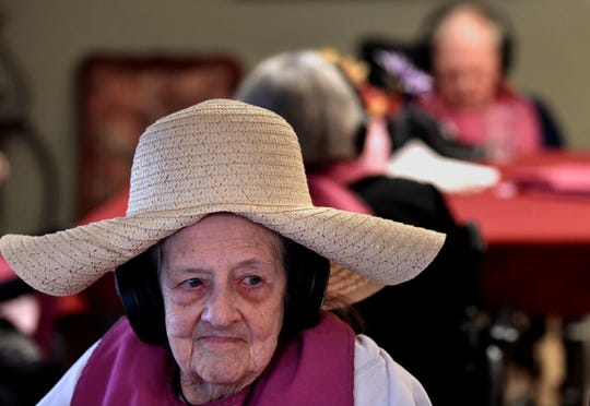 Evaline Scifres enjoys her playlist through the headphones beneath her hat Oct. 31 at HomePlace Manor in Hamlin.