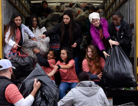 Volunteers load bags of clothing into a truck Friday during Mission: Thanksgiving at Arrow Ford. The day-long donation event benefited Love & Care Ministries.