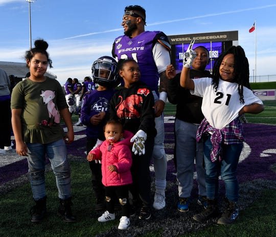 Abilene Christian running back Tracy James poses for a family picture with his nieces and nephews on the field after the home game against Southeastern Louisiana on Nov. 16.