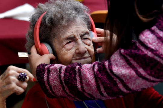 Hamlin High School freshman Heaven Larsen places headphones on Pansy Hale, 101, at HomePlace Manor Oct. 31. Students from the school are participating in a program using music to enhance cognitive ability in nursing home residents.