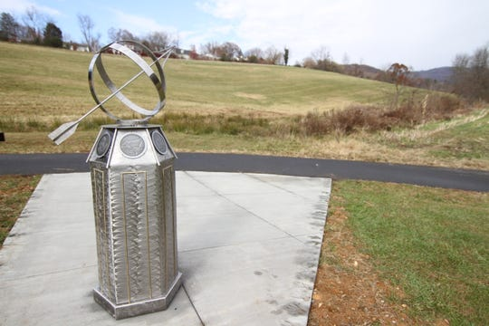 "Tennessee-based artist Mary Ruden's ""Timekeeper"" stands below Mars Hill Elementary School. Hand prints from fifth grade students line line the concrete surrounding the sculpture."
