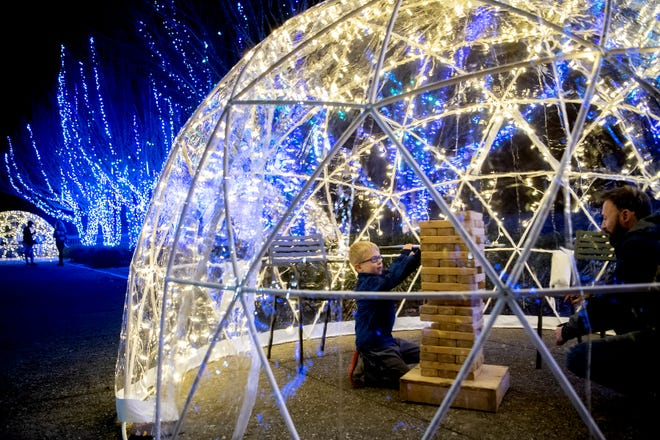 Nate Hess, 6, plays giant Jenga with his dad, Darrell inside an igloo as they attend a preview of the Winter Lights display at the North Carolina Arboretum on Nov. 21, 2019. The display, which has more than 500,000 lights, is open nightly from 6 p.m. to 10 p.m from Nov. 22 to Jan. 4, 2020.