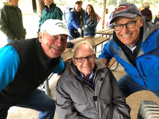 Barney McCallum, center, poses for a picture at the groundbreaking for new pickleball courts at Battle Point Park on Bainbridge Island, with islander Clay Roberts, left, and Gov. Jay Inslee, right.