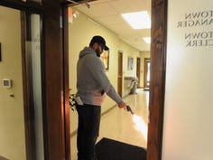 Chris Gomez fires a blank round from a revolver in the Black Mountain Town Hall, Nov. 19, as he plays the role of an active shooter in a training exercise designed to test the town's response to emergency situations.