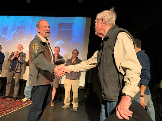 Joe Standaert, left, presents John Buckner with a jacket commemorating Buckner's completion of the 11 hikes on the Swannanoa Rim Explorer Series, one of two popular hiking programs offered by the Swannanoa Valley Museum & History Center.
