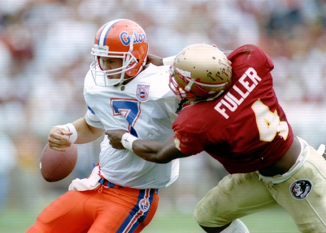 Florida quarterback Danny Wuerffel fumbles the football after being hit by Florida State's Corey Fuller on Nov. 26, 1994.