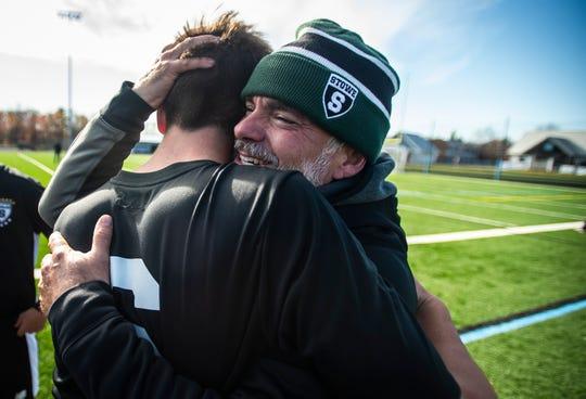Stowe's Alex Tilgner embraces Head Coach Brian Buczek after the Div. 2 Vermont boys soccer championship at South Burlington High School on Saturday, Nov. 2, 2019, Stowe won, 2-0.
