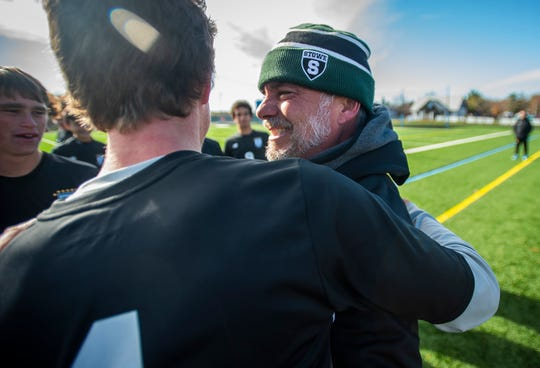 Stowe Head Coach Brian Buczek celebrates with his team after the Div. 2 Vermont boys soccer championship at South Burlington High School on Saturday, Nov. 2, 2019, Stowe won, 2-0.