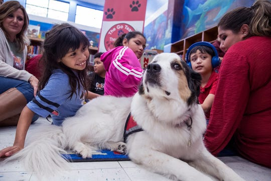 Robstown's Ortiz Intermediate School students Victoria Rojas, from left, 9, Christiana Mungia, 11, and Brody Morales, 11, interact with therapy dogs from The Go Team on Friday, November 22, 2019.